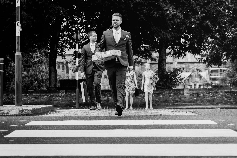 Groomsmen at zebra crossing with flowers