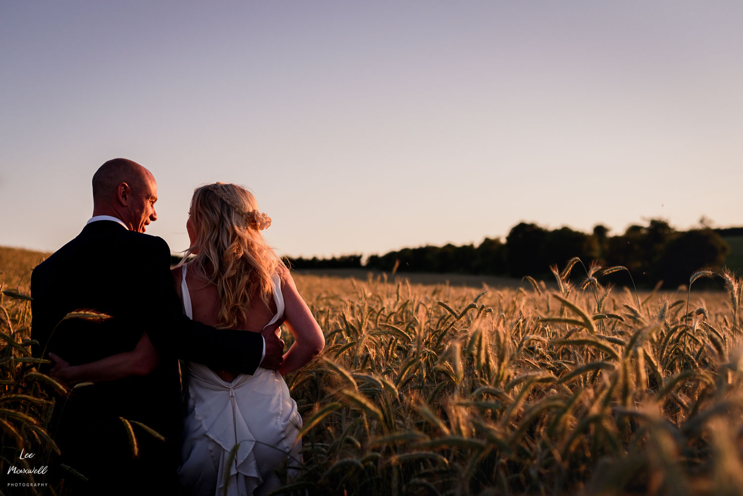 Bride and groom walking at sunset
