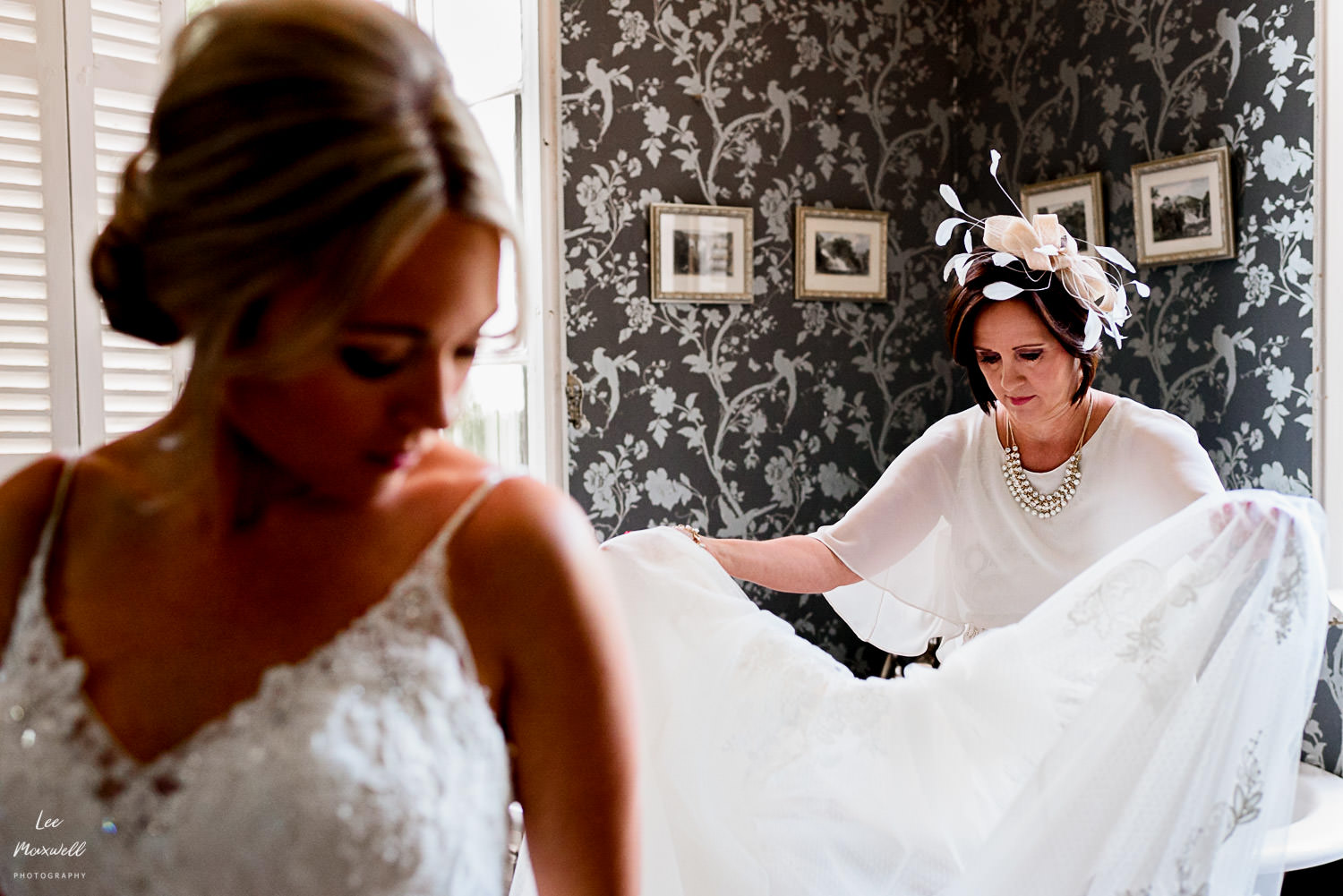Mum helping bride with dress
