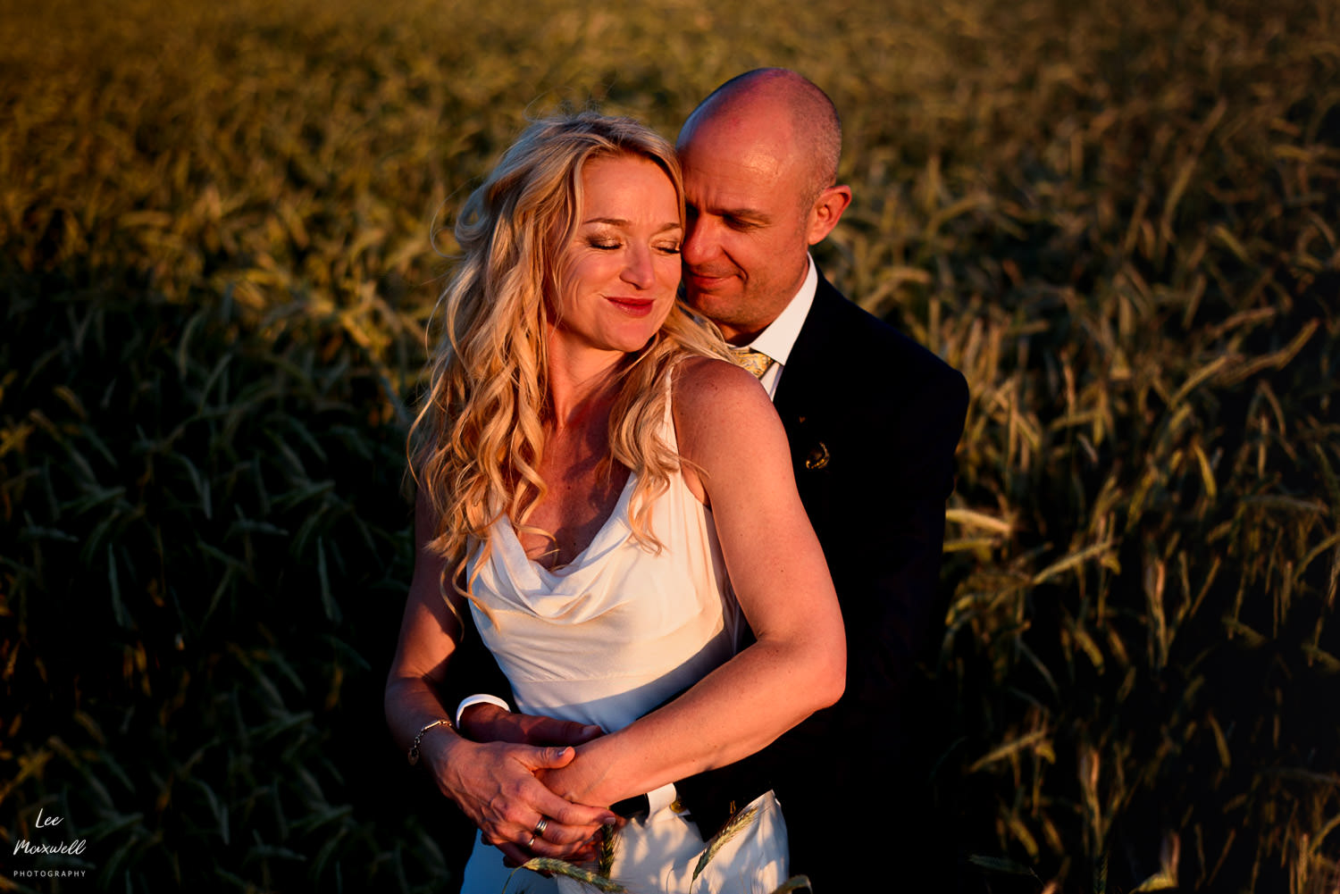 Relaxed wedding portrait in field