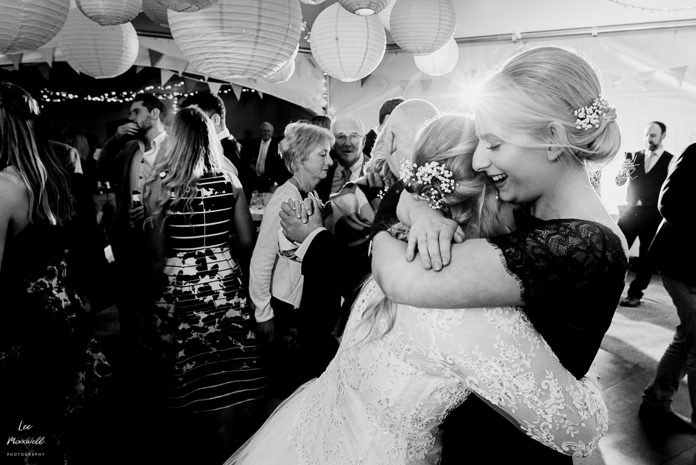 Sister hugging the bride