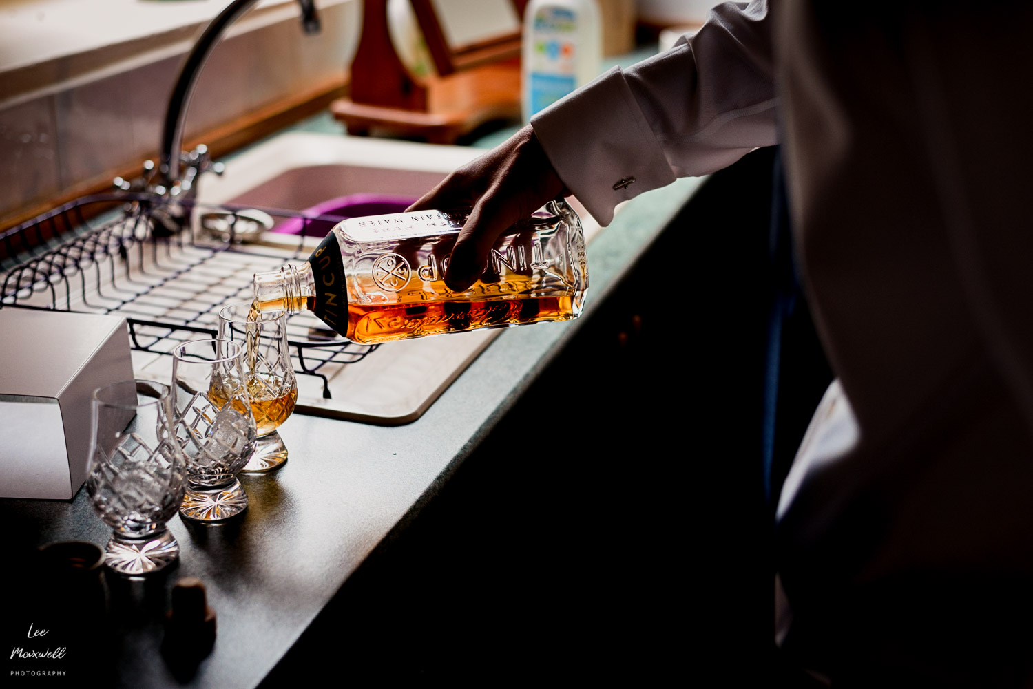 Groom pouring whisky