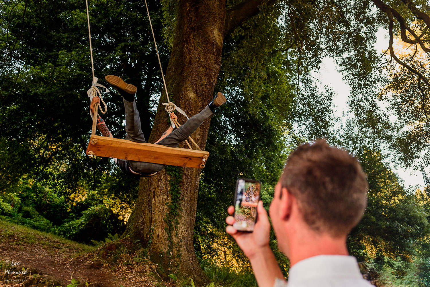 Wedding guest taking photo on swing