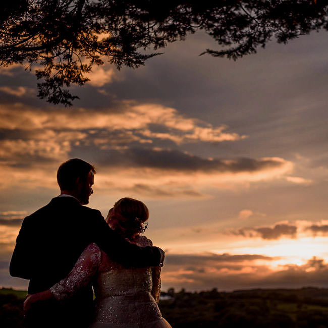 Wedding couple having a hug at sunset