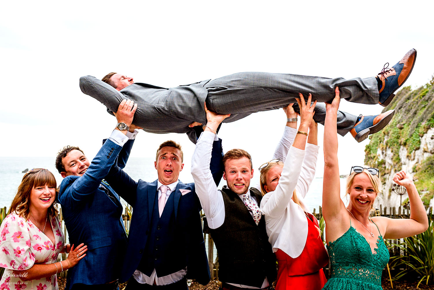 Friends lifting groom in the air