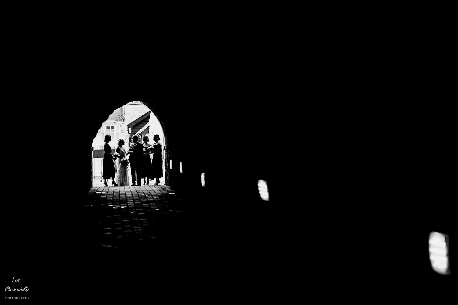 Bridal party walking down tunnel