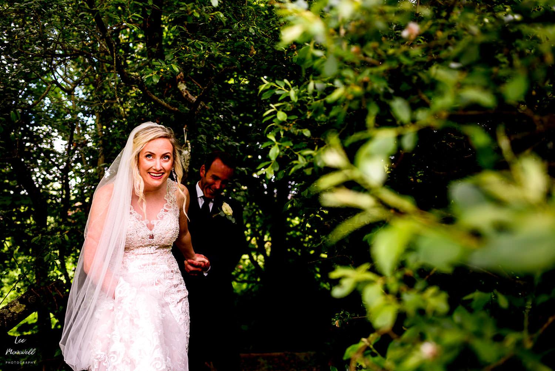 Bride walking through the tree line
