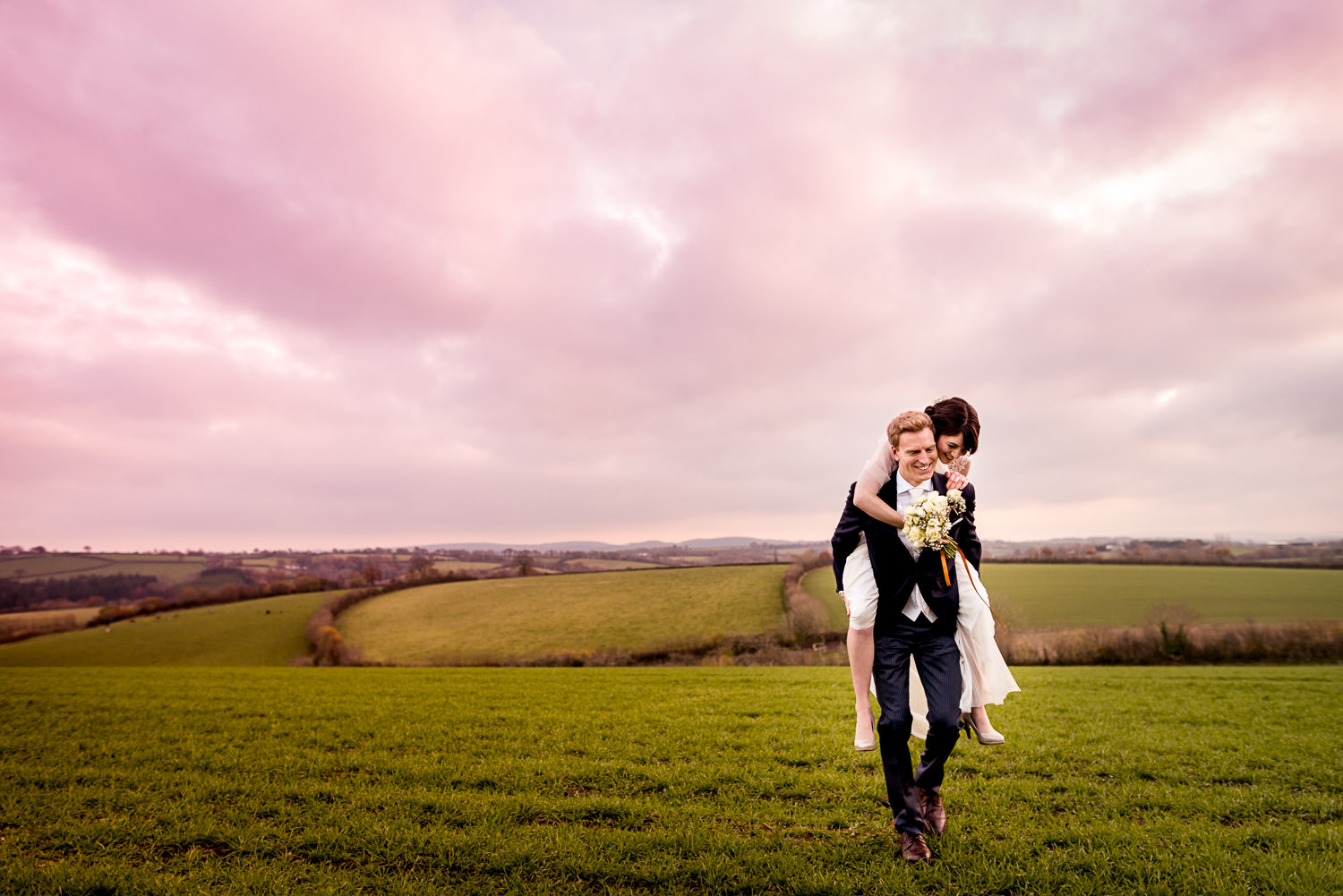 Bride and groom piggy back in Devon