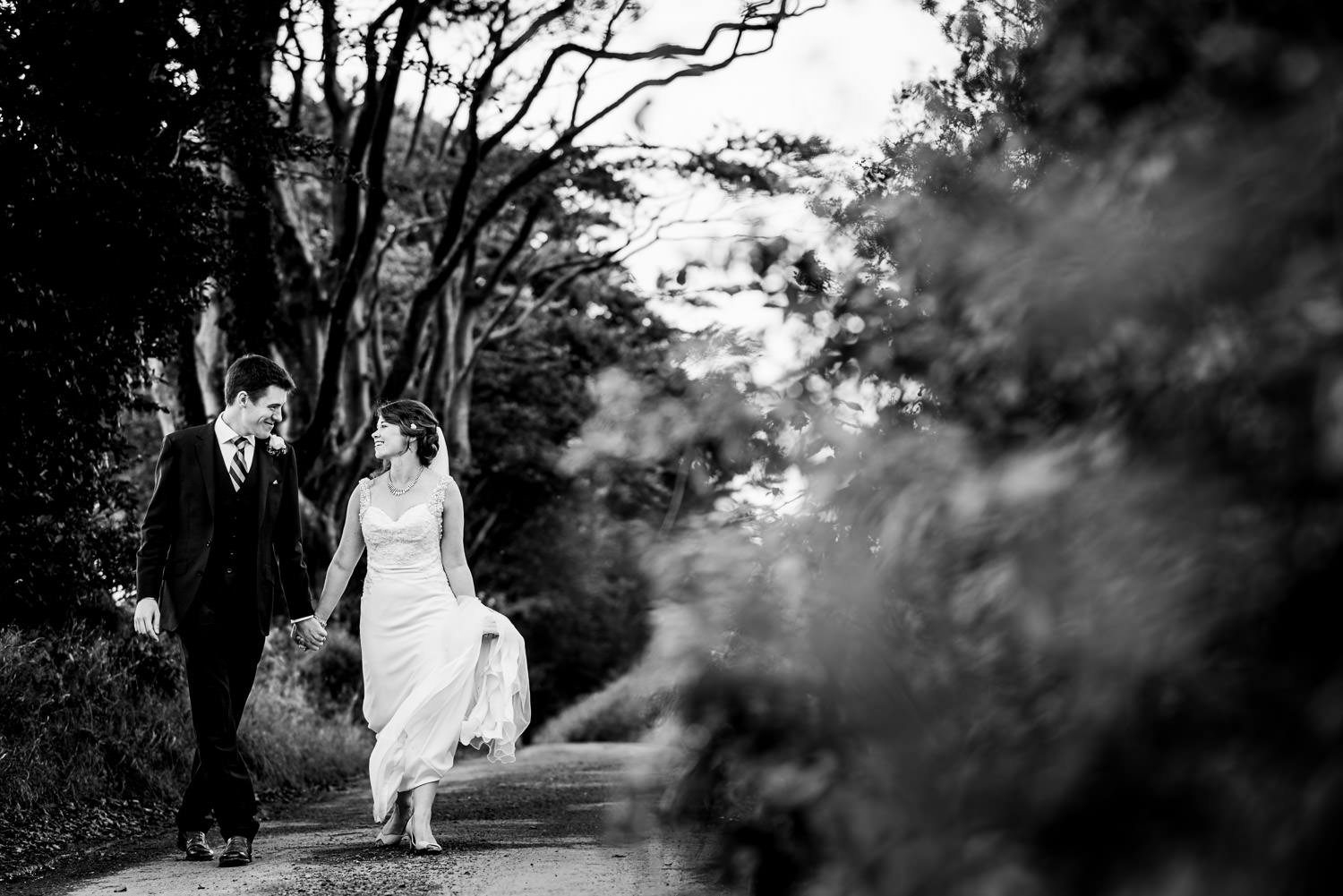 Bride and groom walking Devon country lane